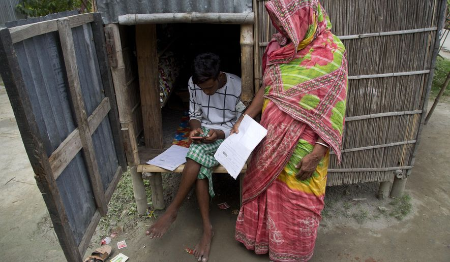 In this Aug. 31, 2019 photo, a man checks names in the final list of National Register of Citizens on his mobile phone as a woman stands waiting to check her name in Buraburi village, Morigaon district, Assam, India. About 1.9 million people were left out of the National Register of Citizens _ a mammoth exercise to weed out illegal mainly Bangladeshi immigrants from Assam's more than 32 million people. (AP Photo/Anupam Nath)