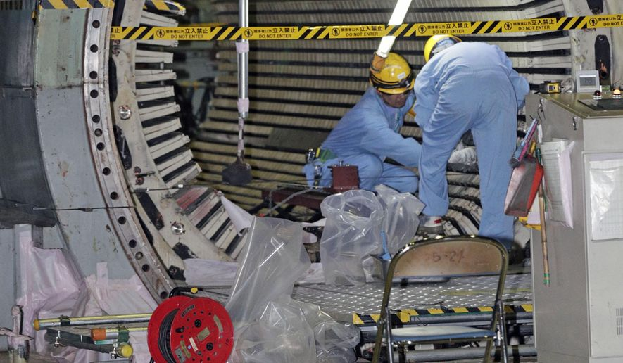 In this Nov. 28, 2018, photo, workers dismantle the Unit 2 reactor at Chubu Electric Power Co.,'s Hamaoka nuclear power plant in Omaezaki, Shizuoka prefecture. Japan's nuclear policy-setting body has adopted a report saying the country is entering an era of massive nuclear plant decommissioning, urging operators to plan ahead to lower safety risks and costs on work requiring decades and billions of dollars. (Kyodo News via AP, File)