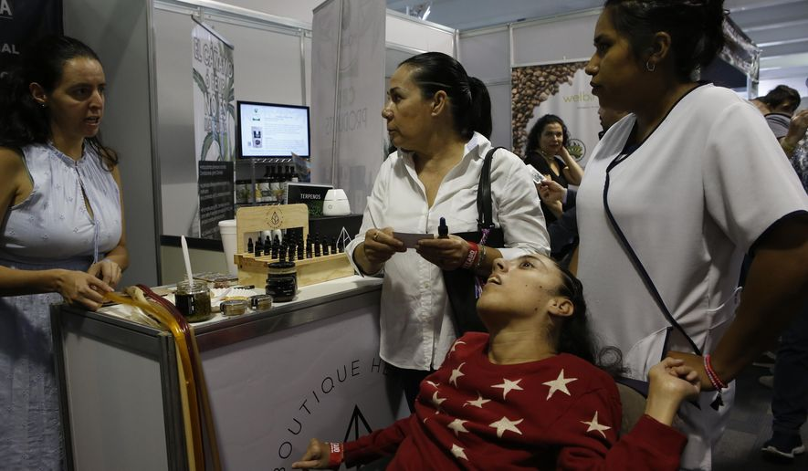 Claudia Gracia, center, listens to a seller while her daughter Paulina, who suffers cerebral paralysis, sits in a wheelchair next to her, during the 4th edition of the ExpoWeed cannabis fair in Mexico City, Saturday, Aug. 31, 2019. ExpoWeed Mexico 2019, is the largest cannabis fair in Mexico and addresses medicinal, industrial and ancestral uses of cannabis. (AP Photo/Ginnette Riquelme)