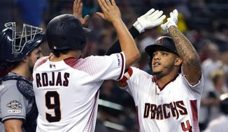 Arizona Diamondbacks' Ketel Marte, right, celebrates with Josh Rojas (9) after hitting a two-run home run in the second inning during a baseball game against the San Diego Padres, Monday, Sept. 2, 2019, in Phoenix. (AP Photo/Rick Scuteri)