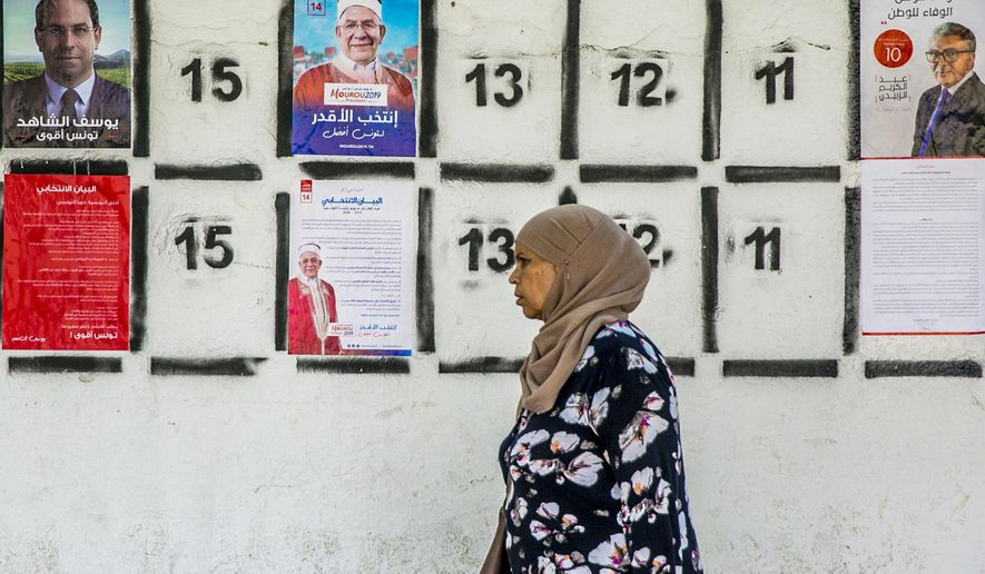 A woman walks past a wall of campaign posters in Tunis, Tunisia, Monday, Sept. 2, 2019.Tunisia's 26 presidential candidates have launched their campaigns in a political climate marked by uncertainty, money laundering allegations and worries about violent extremism. (AP Photo/Hassene Dridi)