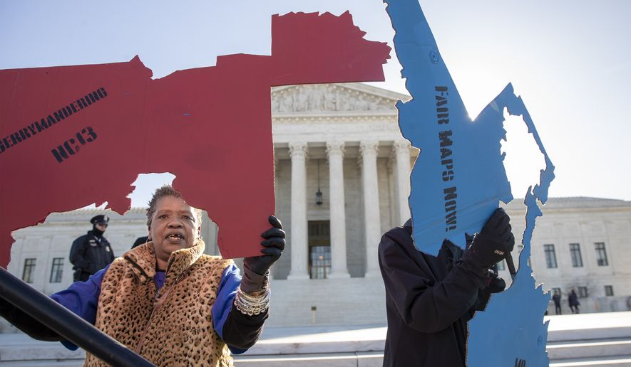 Activists at the Supreme Court opposed to partisan gerrymandering hold up representations of congressional districts from North Carolina, left, and Maryland, right, as justices hear arguments about the practice of political parties manipulating the boundary of a congressional district to unfairly benefit one party over another, in Washington, Tuesday, March 26, 2019. Democrats and Republicans eagerly await the outcome of cases from Maryland and North Carolina because a new round of redistricting will follow the 2020 census, and the decision could help shape the makeup of Congress and state legislatures over the next decade. (AP Photo/Carolyn Kaster)