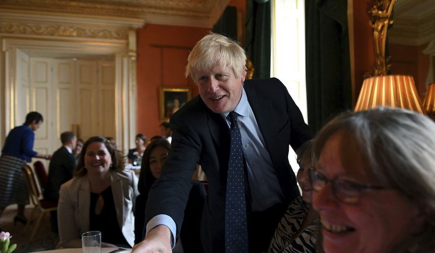 "Britain's Prime Minister Boris Johnson speaks with NHS workers during a reception at 10 Downing Street, London, Tuesday, Sept. 3, 2019. Britain's opposition leader has attacked Prime Minister Boris Johnson for trying to run a ""cabal"" from Downing Street in order to take Britain out of the European Union without a deal despite the costs. (Daniel Leal-Olivas/Pool Photo via AP)"