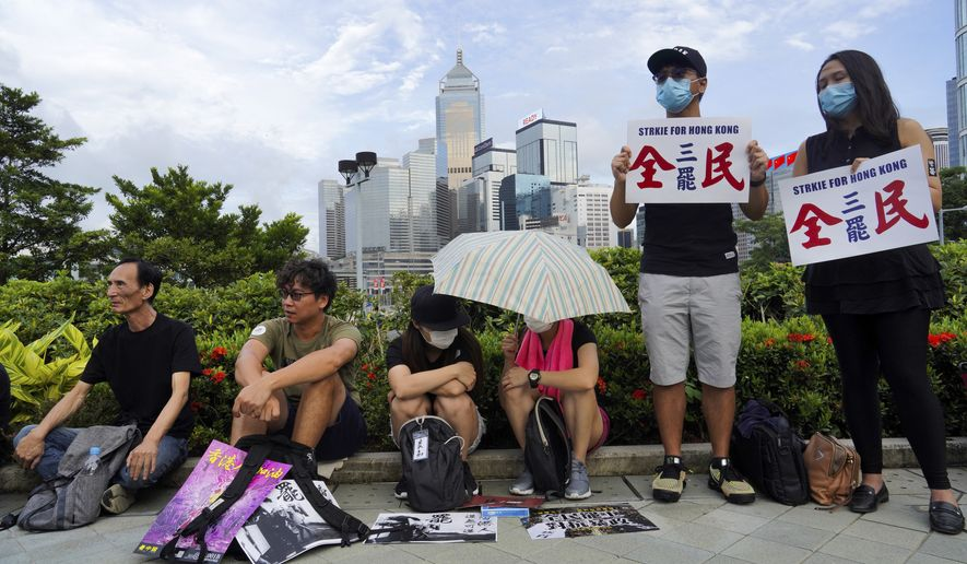"""Protesters hold placard read """"Strike for Hong Kong"""" as others listens to speech during continuing pro-democracy rallies in Tamar Park, Hong Kong, on Tuesday, Sept. 3, 2019. Hong Kong leader Carrie Lam said Tuesday she has never tendered her resignation to China over the anti-government protests that have roiled the city for three months. (AP Photo/Vincent Yu)"""