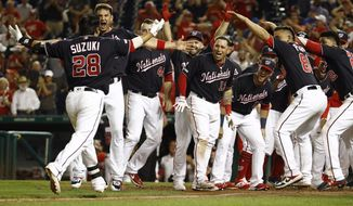 Washington Nationals greet Kurt Suzuki (28) as he approaches home plate after hitting a game-winning three-run home run in the team's baseball game against the New York Mets, Tuesday, Sept. 3, 2019, in Washington. Washington won 11-10. (AP Photo/Patrick Semansky)