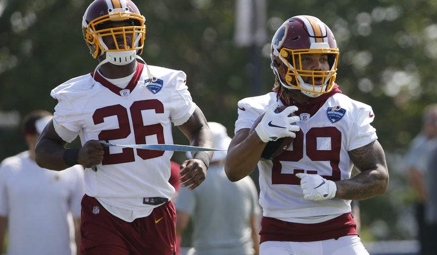 FILE - In this Friday, July 26, 2019, file photo, Washington Redskins running backs Derrius Guice (29) and Adrian Peterson (26) run drills during the NFL football training camp in Richmond, Va. Adrian Peterson told Derrius Guice to grab some ice cubes and wrap them around his surgically repaired left knee. Guice chuckled a bit. You're really old school, Guice said. We got all this Cryotherapy and stuff, and you're talking about bags of ice. Old school, meet new school in the Redskins backfield headlined by a 34-year-old climbing the all-time rushing list and a 22-year-old itching to make his NFL debut 13 months after a torn ACL. (AP Photo/Steve Helber) ** FILE **