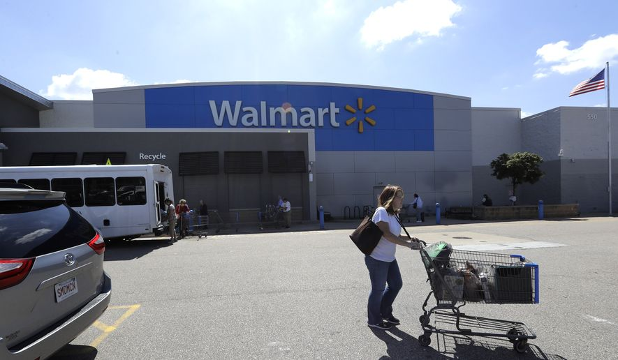A customer pushes a shopping cart Tuesday, Sept. 3, 2019, outside a Walmart store, in Walpole, Mass. Walmart is going back to its folksy hunting heritage and getting rid of anything that's not related to a hunting rifle after two mass shootings in its stores in one week left 24 people dead in August of 2019. (AP Photo/Steven Senne)