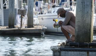 James Miranda, right, of Santa Barbara, holds flowers and takes a moment to reflect at a dock near the Sea Landing at Santa Barbara Harbor in Santa Barbara, Calif., Monday, Sept. 2, 2019. A fire raged through a boat carrying recreational scuba divers anchored near an island off the Southern California coast early Monday, leaving multiple people dead and hope diminishing that any of the more than two dozen people still missing would be found alive. (AP Photo/Ringo H.W. Chiu)