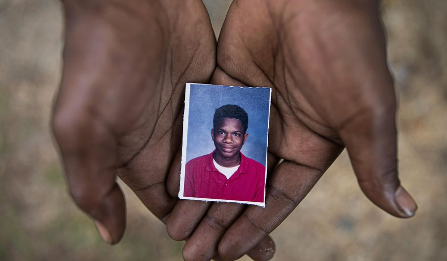 Joshua K. Love, 36, holds a photograph of himself taken at about the time he says he was sexually abused at St. Francis of Assisi School by two Franciscan friars, Brother Paul West and the late Brother Donald Lucas, in Greenwood, Miss., Monday, June 10, 2019. (AP Photo/Wong Maye-E)