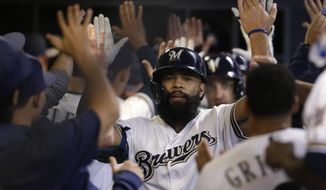 Milwaukee Brewers' Eric Thames is congratulated in the dugout after his three-run home run against the Houston Astros during the third inning of a baseball game Tuesday, Sept. 3, 2019, in Milwaukee. (AP Photo/Jeffrey Phelps)