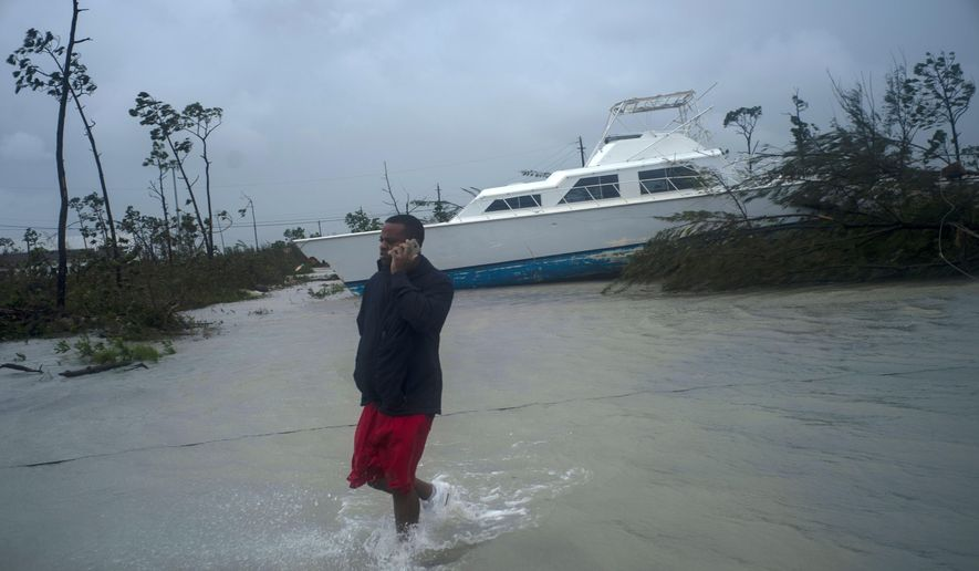 A man talks on his mobile phone next to a catamaran that was thrown onshore by the Hurricane Dorian near highway close Freeport, Grand Bahama, Bahamas, Tuesday Sept. 3, 2019. Relief officials reported scenes of utter ruin in parts of the Bahamas and rushed to deal with an unfolding humanitarian crisis in the wake of Hurricane Dorian, the most powerful storm on record ever to hit the islands. (AP Photo/Ramon Espinosa)