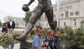 The grandchildren of Chicago Bears and Pro Football Hall of Fame running back Walter Payton pose under his newly dedicated statue after an unveiling ceremony outside Soldier Field of statues honoring George Halas and Payton Tuesday, Sept. 3, 2019, in Chicago. (AP Photo/Charles Rex Arbogast)