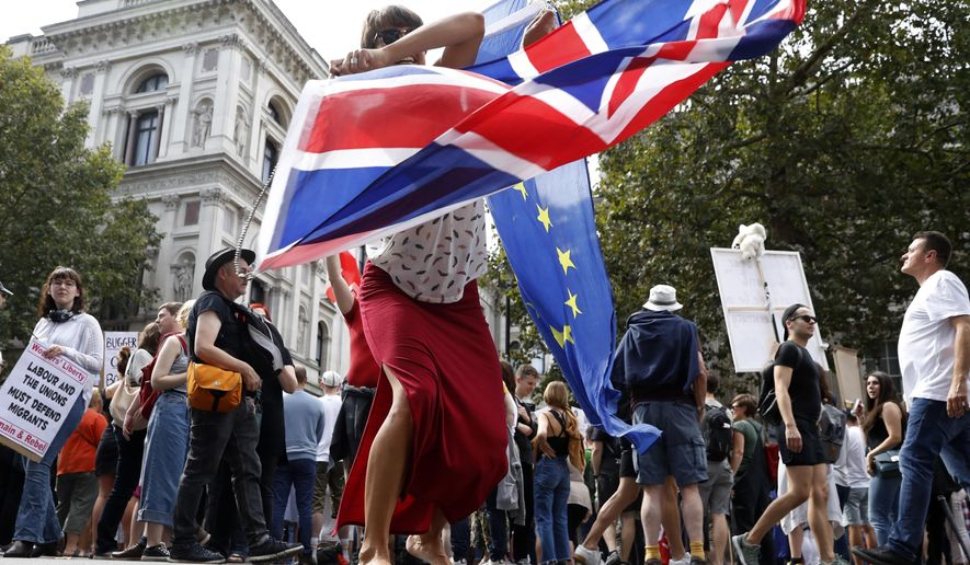 An anti Brexit protester waves the flags of European Union and Britain during a rally outside Downing Street in London, Saturday, Aug. 31, 2019. Political opposition to Prime Minister Boris Johnson's move to suspend Parliament is crystalizing, with protests around Britain and a petition to block the move gaining more than one million signatures. (AP Photo/Alastair Grant)