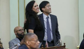 State Sen. Richard Pan, D-Sacramento, smiles as he and Assemblywoman Lorena Gonzalez, D-San Diego, watch as the votes are posted for his measure to tighten the rules on giving exemptions for vaccinations was approved by the Assembly in Sacramento, Calif., Tuesday, Sept. 3, 2019. The Assembly approved the bill SB276, that would give state public health officials oversight of doctors who give more than five medical exemptions annually and schools with vaccination rates less than 95%. It still needs a final approval in the state Senate. (AP Photo/Rich Pedroncelli)