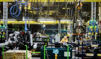 FILE - In this June 12, 2019, file photo General Motors employees work on the chassis line as they build the frame, power train and suspension onto the truck's body at the Flint Assembly Plant in Flint, Mich. On Tuesday, Sept. 3, the Institute for Supply Management, a trade group of purchasing managers, issues its index of manufacturing activity for August. (Jake May/The Flint Journal via AP, File)