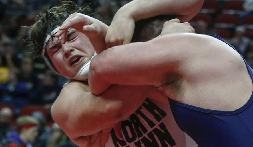 FILE - In this Feb. 18, 2017, file photo, North Linn's Kyler Schott, left, wrestles Iowa City Regina's Jared Brinkman in their 285-pound title match during the state Class 1A finals in Des Moines, Iowa. Schott is slated to make his first career NCAA college football start for Iowa against Rutgers on Saturday. Schott earned all-state honors in football and on the mat for North Linn High. (Bryon Houlgrave/The Des Moines Register via AP, File )