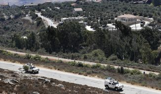 Spanish UN peacekeepers patrol along the Lebanese-Israeli border, with the Israeli village of Metulla, background, in the village of Kfar Kila, Lebanon, Monday, Sept. 2, 2019. The Lebanon-Israel border was mostly calm with U.N. peacekeepers patrolling the border Monday, a day after the Lebanese militant Hezbollah group fired a barrage of anti-tank missiles into Israel, triggering Israeli artillery fire that lasted less than two hours and caused some fires. (AP Photo/Hussein Malla)