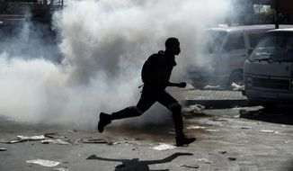 A man runs away from teargas after making off with goods from a store in Germiston, east of Johannesburg, South Africa, Tuesday, Sept. 3, 2019. Police had earlier fired rubber bullets as they struggled to stop looters who targeted businesses as unrest broke out in several spots in and around the city. (AP Photo/Themba Hadebe)