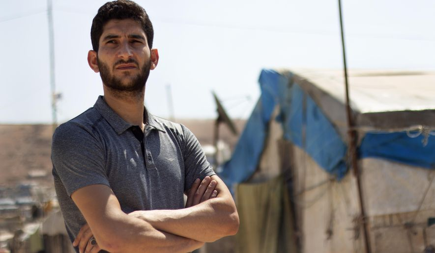 """In this Sunday Sept. 1, 2019 photo, Syrian Abdel Hamid al-Yousef poses for a picture, at a displaced settlement near the Turkish border called """"Mokhayyam al-Karamah,"""" Arabic for """"Dignity Camp,"""" near the town of Atmeh, in northern Syria. Al-Yousef lost his baby twins, his wife and 16 other relatives in the poison gas attack that hit Syria's Khan Sheikhoun in April 2017. Determined to continue with his life, he remarried, and has an 11-month-old daughter. But tragedy keeps chasing the 31-year-old former shopkeeper as he recently fled a government assault on Idlib and the nonstop bombardment of Khan Sheikhoun. (AP Photo)"""