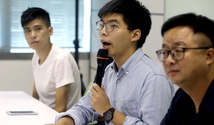 Hong Kong activist Joshua Wong, center, talks to the press with Taiwan Democratic Progressive Party (DPP) Secretary-General Luo Wen-jia, right, after meeting DPP political leaders in Taipei, Taiwan, Tuesday, Sept. 3, 2019. Joshua Wong visits pro-democracy political leaders and joint forum during a two-days trip from Tuesday in Taiwan. (AP Photo/ Chiang Ying-ying)