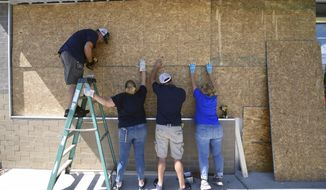 Jared Rogers, from left, Christine Bright, Stephen Bright and Marie Rogers board up a Family Dollar story in Wilmington, N.C., Tuesday, Sept. 3, 2019, as residents make preparations for Hurricane Dorian. (Matt Born/The Star-News via AP)