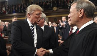 In this Feb. 28, 2017, file photo, President Donald Trump shakes hands with Supreme Court Chief Justice John Roberts as he arrives on Capitol Hill in Washington, for his address to a joint session of Congress. (Jim Lo Scalzo/Pool Image via AP, File)