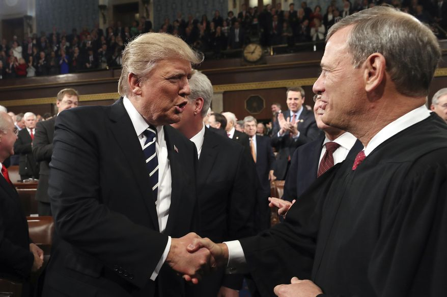 In this Feb. 28, 2017, photo, President Donald Trump shakes hands with Supreme Court Chief Justice John Roberts as he arrives on Capitol Hill in Washington, for his address to a joint session of Congress. (Jim Lo Scalzo/Pool Image via AP) **FILE**