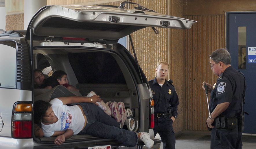 United States Customs and Border Protection officers watch as a group of 14 people, who were found hiding in a 2004 Chevrolet Suburban SUV, unload from the car in the San Ysidro Port of Entry secondary inspection on Tuesday, June 13, 2006, in San Diego, California. (AP Photo/David Maung) ** FILE **