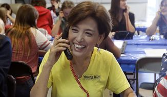 Young Kim, left, the Republican candidate for the 39th Congressional District in California, smiles as a bell rings at her headquarters in Yorba Linda, Calif., Tuesday, Nov. 6, 2018. (AP Photo/Alex Gallardo) ** FILE **