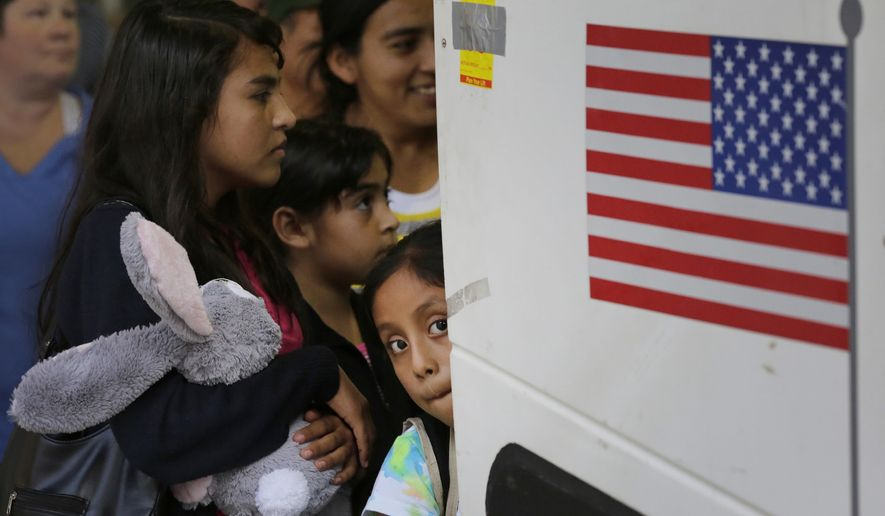 In this July 7, 2015 file photo, immigrants from El Salvador and Guatemala who entered the country illegally board a bus after they were released from a family detention center in San Antonio. Attorneys on Friday, Aug. 30, 2019, asked a judge to reject Trump administration plans to detain migrant families longer than they're allowed now and to remove court oversight of how children are treated in government custody.  (AP Photo/Eric Gay, File)