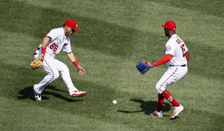 Washington Nationals right fielder Gerardo Parra, left, and center fielder Victor Robles, right, chase after New York Mets' Amed Rosario's fly ball single that Robles committed an error while attempting to field in the sixth inning of a baseball game, Wednesday, Sept. 4, 2019, in Washington. J.D. Davis and Robinson Cano scored on the play. (AP Photo/Patrick Semansky)