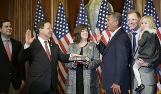 In this Jan. 6, 2015, file photo, then House Speaker John Boehner of Ohio, right, administers the House oath to Rep. Bill Flores, R-Texas, during a ceremonial re-enactment swearing-in ceremony in the Rayburn Room on Capitol Hill in Washington. Joining them are Flores' wife Gina and other family members. Flores won't run for re-election in 2020, becoming the state's fifth Republican congressman to say he's leaving. His announcement brings the number of House Republicans retiring next year to 15. (AP Photo/Pablo Martinez Monsivais, File) **FILE**