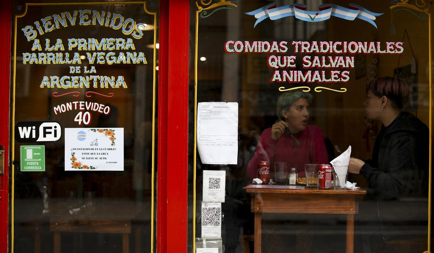"""People eat at """"La Reverde"""" vegan restaurant in Buenos Aires, Argentina, Friday, June 30, 2019. At Buenos Aires' first vegan grill, the house specialty resembles the country's bife de chorizo, a popular cut of boneless beef cooked on a grill. (AP Photo/Natacha Pisarenko)"""