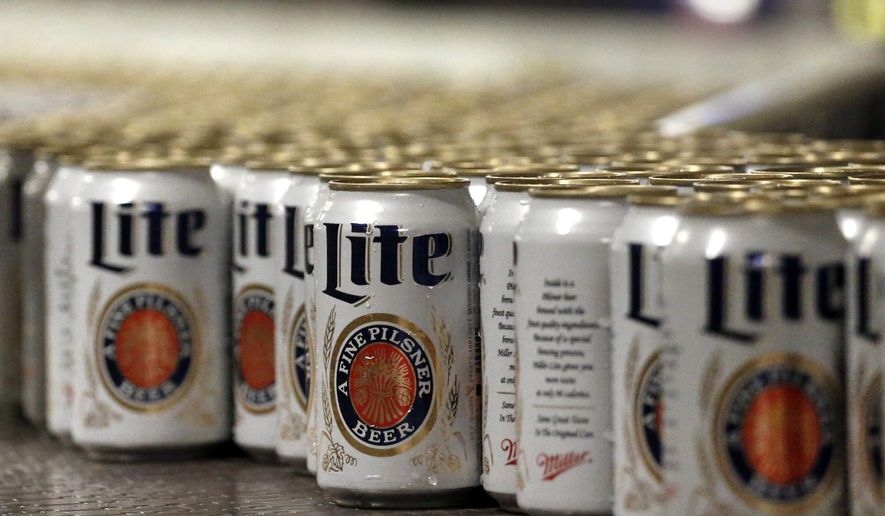 """FILE - In this March 11, 2015 file photo, newly-filled and sealed cans of Miller Lite beer move along on a conveyor belt, at the MillerCoors Brewery, in Golden, Colo. A federal judge has ordered Anheuser-Busch to stop using packaging that implies MillerCoors' light beers contain corn syrup. U.S. District Judge William Conley granted a preliminary injunction sought by MillerCoors. Bud Light's packaging says """"No Corn Syrup"""" in bold letters. (AP Photo/Brennan Linsley, File)"""