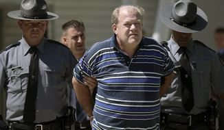 In this Tuesday, Sept. 3, 2019 photo, Pennsylvania state troopers lead Theodore Dill Donahue out of the Pennsylvania State Police Troop K barracks in West Philadelphia after arresting him as a suspect in the 1991 murder of Denise Sharon Kulb. (Tim Tai/The Philadelphia Inquirer via AP)