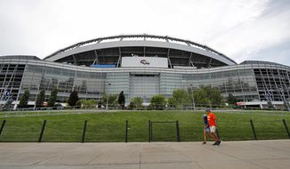 """FILE - In this Aug. 29, 2019, file photo, fans pass by the east side of Mile High Stadium before an NFL preseason football game between the Arizona Cardinals and the Denver Broncos in Denver. The Broncos announced Wednesday, Sept. 4, 2019, that the team will partner with Colorado-based Empower Retirement on a 21-year deal to name the stadium """"Empower Field at Mile High."""" (AP Photo/David Zalubowski, File)"""