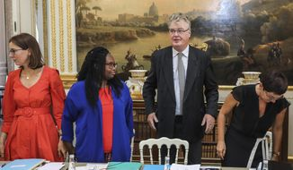 Newly appointed French High Commissioner for Pension Reform Jean-Paul Delevoye, center, stands by French Junior Minister for European Affairs Amelie de Montchalin, left, French Government's spokesperson Sibeth Ndiaye, second left and French Overseas Minister Annick Girardin, at the start of his first cabinet meeting at the Elysee Palace in Paris, France, Wednesday Sept. 4, 2019. French President Emmanuel Macron is holding a special government meeting to outline his domestic agenda for the coming year, including a controversial overhaul of the pension system. (Ludovic Marin/Pool Photo via AP)