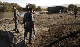FILE - In this Saturday, Sept. 5, 2009 file photo Afghan police secures the spot where villagers reportedly died when American jets bombed fuel tankers hijacked by the Taliban, outside Kunduz, Afghanistan. The top U.S. and NATO commander in Afghanistan visited the site as the alliance began an investigation into the airstrike that killed up to 70 people. Lawyers acting on behalf of relatives who lost family members say they are still trying to get adequate compensation for their clients and hope to hold the German commander who ordered the Sept. 4, 2009, air strike criminally responsible. (AP Photo/Anja Niedringhaus, file)