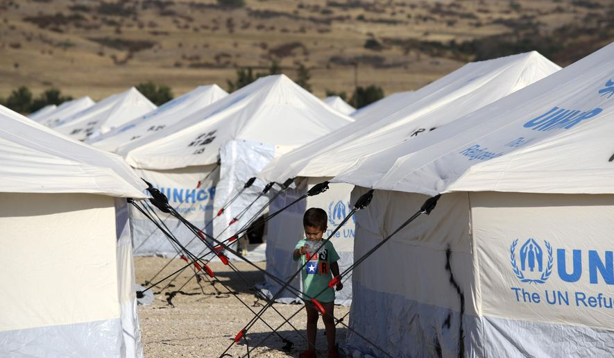 A migrant boy stands outside a tent at a refugee camp in Nea Kavala, northern Greece, Tuesday, Sept. 3, 2019. About 1,500 asylum-seekers transported from Greece's eastern Aegean island of Lesbos to the mainland. Around 1,000 of those transferred and housed in Nea Kavala, where they will be staying in tents until the end of the month, after which they will be transferred to a new camp under construction. (AP Photo/Giannis Papanikos)
