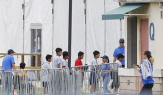 In this June 20, 2018 photo, immigrant children walk in a line outside the Homestead Temporary Shelter for Unaccompanied Children, a former Job Corps site that now houses them in Homestead, Fla. (AP Photo/Brynn Anderson, File)