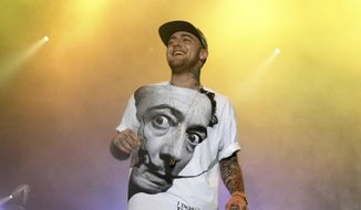 FILE - In this July 13, 2013, file photo, rapper Mac Miller performs on his Space Migration Tour in Philadelphia. A man has been charged with selling counterfeit opioid pills to Mac Miller two days before the rapper died of an overdose.  An autopsy found that the 26-year-old Miller died in his Los Angeles home on Sept. 7 from a combination of fentanyl, cocaine and alcohol.  (Photo by Owen Sweeney/Invision/AP, File)