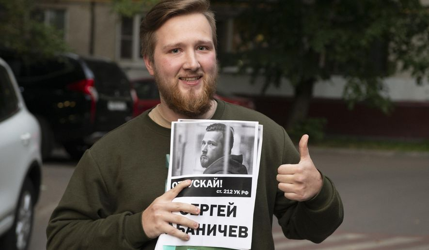 "In this photo taken on Tuesday, Sept 3, 2019, Sergei Abanichev holds a banner with portrait of him reading ""release!"", upon his release in Moscow, Russia. Abanichev is one of five people charged with rioting related to this summer's anti-government protest who had the charges against them abruptly dropped. (AP Photo/Dmitry Serebryakov)"