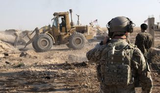 In this Aug. 22, 2019, file photo, provided by the U.S. Army, shows A U.S. service member watches as Syrian Democratic Forces remove military fortifications during the implementation of the security mechanism along the Turkey-Syria border in northeast Syria. (Spc. Alec Dionne/U.S. Army via AP ) ** FILE **