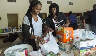 Volunteers Jazz Williams, 29, left, and Jodye Scavella, 47, organize donated goods for those affected by Hurricane Dorian in the Bahamas, at Christ Episcopal Church in Miami, Tuesday, Sept. 3, 2019. Members of two historically black churches are sorting and preparing the supplies to be flown to the hurricane-ravaged islands of Abaco and Grand Bahama. (AP Photo/Ellis Rua)