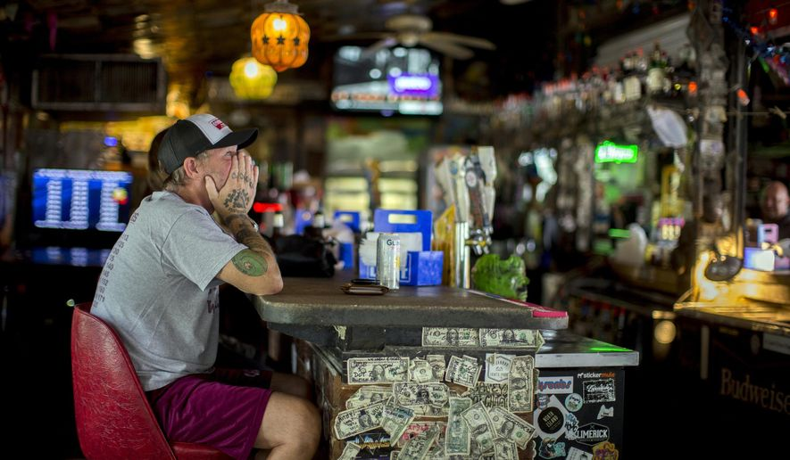 Andrew Parker watches the latest on Hurricane Dorian from the bar at Huc-A-Poos pizza restaurant, Wednesday, Sept. 4, 2019, in Tybee Island, Ga. Parker said he's been through eight hurricanes in his lifetime as a resident of Tybee. And like the others Parker said he plans on riding Dorian out at his home on the island. (AP Photo/Stephen B. Morton)