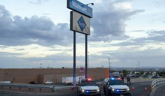 FILE - In this Aug. 3, 2019, photo texas state police cars block the access to the Walmart store in the aftermath of a mass shooting in El Paso, Texas. The Bentonville, Arkansas-based discounter says Tuesday, Sept. 3, that it will be discontinuing the sale of short-barrel and handgun ammunition. (AP Photo/Andres Leighton, File)
