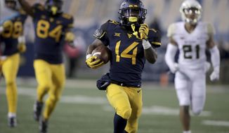 FILE - In this Oct. 25, 2018, file photo, West Virginia running back Tevin Bush (14) runs for a touchdown during the first half of an NCAA college football game against Baylor, in Morgantown, W.Va. Bush set career highs of four catches for 74 yards in a 20-13 win over James Madison and will be looking for more when the Mountaineers travel to face Missouri on Saturday. (AP Photo/Raymond Thompson, File)