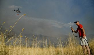 Greg Robbins does his part in trying to add some moisture to tall brush behind his house as crews battle a grass fire in Tooele, Utah being dubbed the Green Ravine fire as it burns on Tuesday, Sept. 3, 2019. (Francisco Kjolseth/The Salt Lake Tribune via AP)