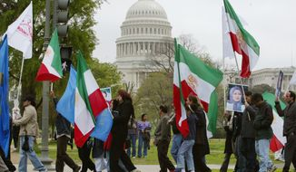 Members of the Iranian-American community hold posters of Maryam Rajavi, President-elect of the National Council of Resistance of Iran (NCRI), along with the Iranian flag and resistance flags, march past the Capitol during a protest in Washington Saturday, April 19, 2003. The demonstrators were calling for urgent action by international bodies to stop Tehran's attacks on the bases of the People's Mojahedin Organization, which is the main resistance group to the current Iranian government, based along the Iran-Iraq border. (AP Photo/Charles Dharapak)