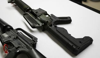 In this Jan. 11, 2018, file photo, a semi-automatic rifle at right that has been fitted with a so-called bump stock device to make it fire faster sits on a table at the Washington State Patrol crime laboratory in Seattle. (AP Photo/Ted S. Warren) ** FILE **